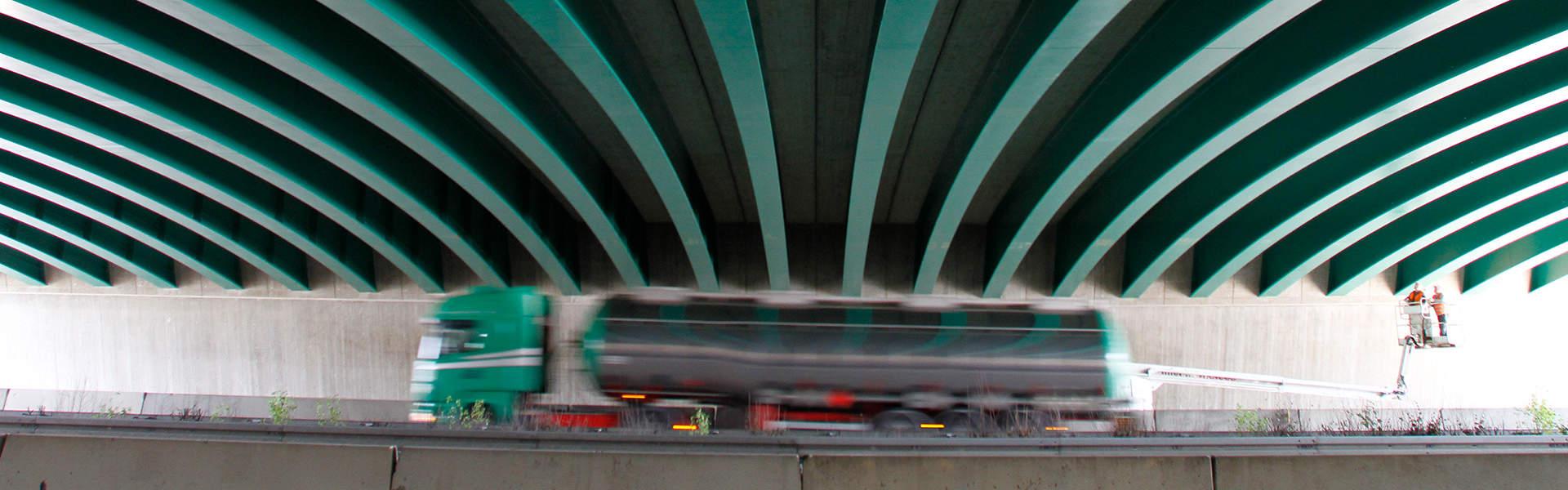 LKW fährt unter einer Brücke